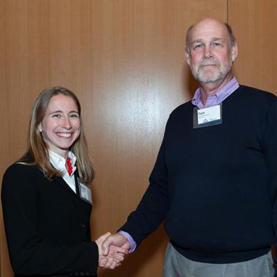 Head judge Tom Fitzsimons, CEO of Kerathin LLC, congratulates Y-Prize winner Emily Plumb.